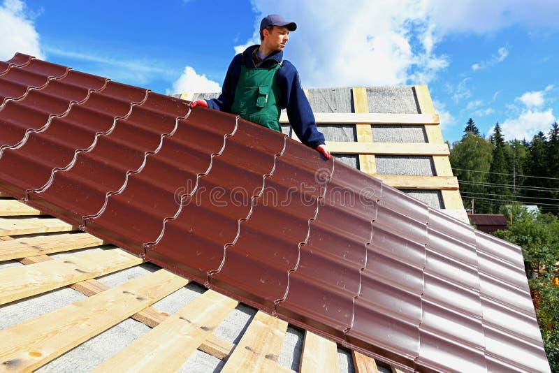 工作者在屋顶上把金属瓦片放 免版税库存照片