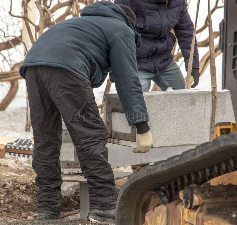 工作者在工地工作拿着混凝土板 免版税库存照片