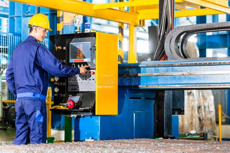 工作者在机器控制盘区的制造工厂 免版税库存图片