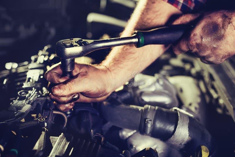 工作者在汽车修理中心修理一辆汽车 库存照片