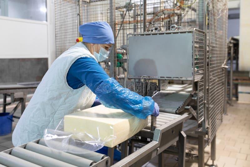工作者在牛奶店包装黄油 免版税图库摄影