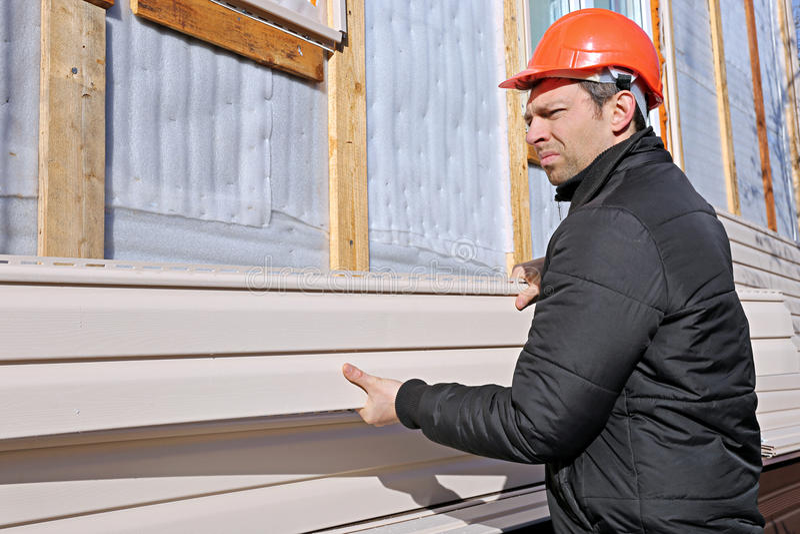 工作者在门面安装盘区米黄房屋板壁 库存图片