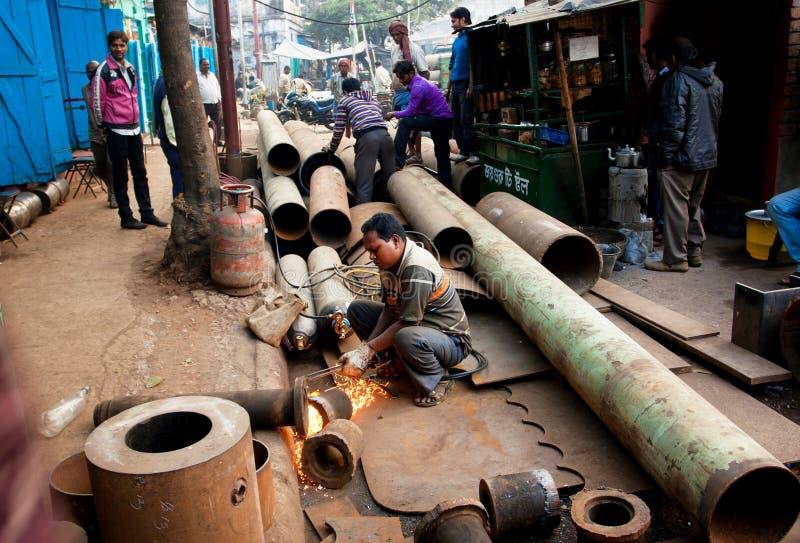 工作者在仓库钢s附近的焊接金属管子 免版税库存图片