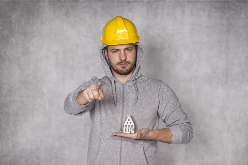 工作者在他的手上举行一个房子和指向您 免版税库存照片