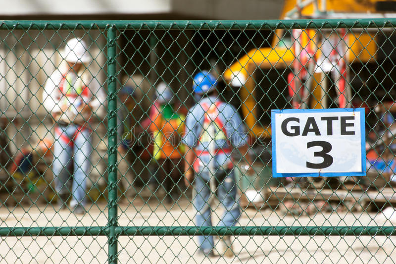 工作者在建造场所,在链节篱芭的焦点 免版税库存图片