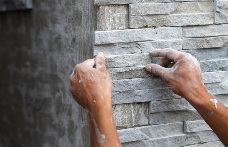 工作者安装与水泥的石墙表面房子的 免版税库存照片
