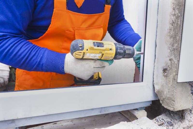 工作者安装塑料窗口和门 免版税库存照片