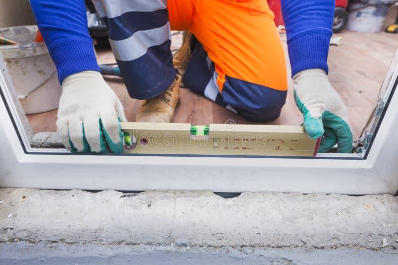 工作者安装塑料窗口和门 库存照片