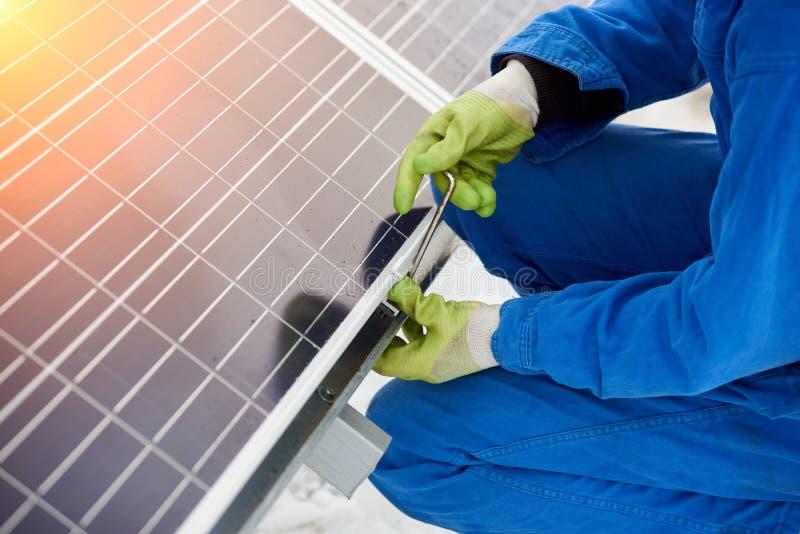 工作者安装太阳能电池使用工具在积雪的天气 免版税库存图片