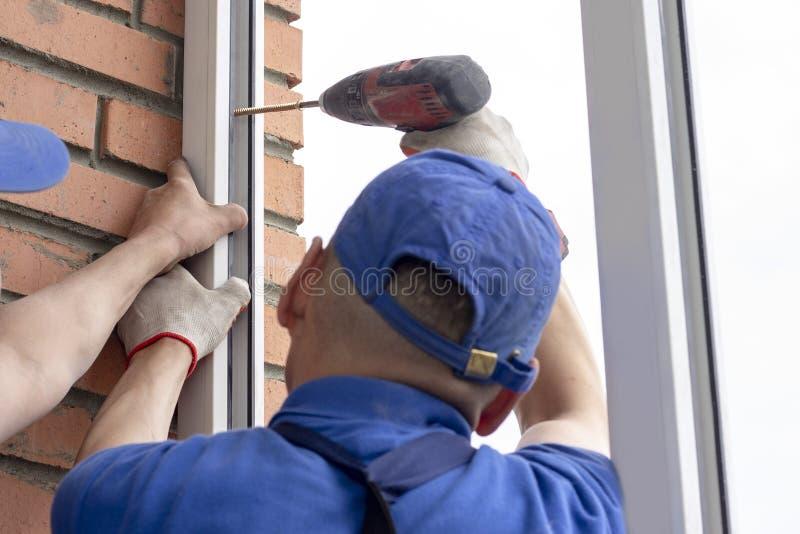 工作者安装工匠拧紧框架对在高层建筑物的墙壁修理的窗口 库存图片