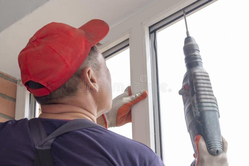 工作者安装工匠拧紧框架对在高层建筑物的墙壁修理的窗口 免版税图库摄影