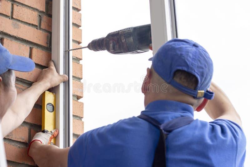 工作者安装工匠拧紧框架对在高层建筑物的墙壁修理的窗口 免版税库存图片