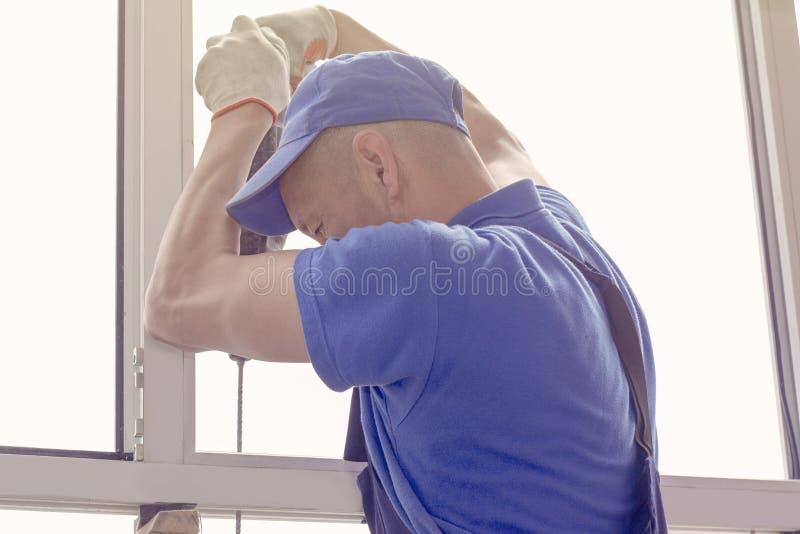 工作者安装窗口主要sverdit框架附有根据在高层建筑物的修理 免版税库存图片