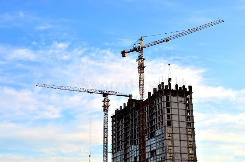 工作者工业建筑用起重机和剪影在模板的设施时 库存图片
