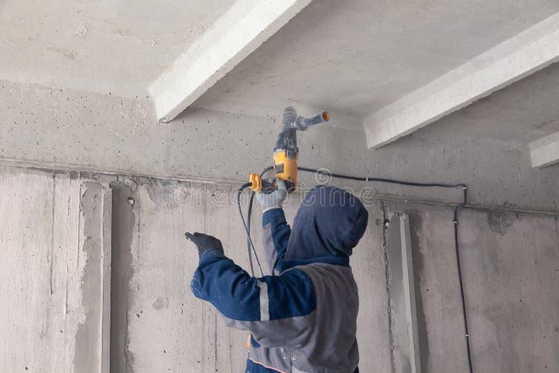工作者建造者做电子接线,钻子与钻子的天花板 概念危险工作,高压,电工,工程师 免版税图库摄影