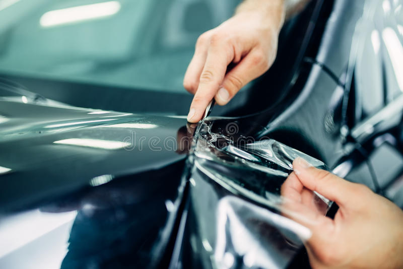 工作者手安装汽车油漆保护影片 库存图片