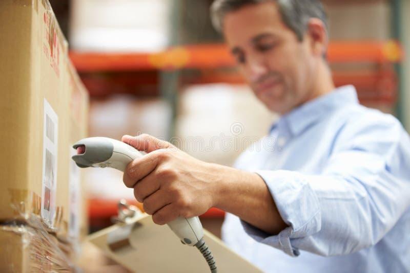工作者扫描包裹在仓库里 免版税库存图片