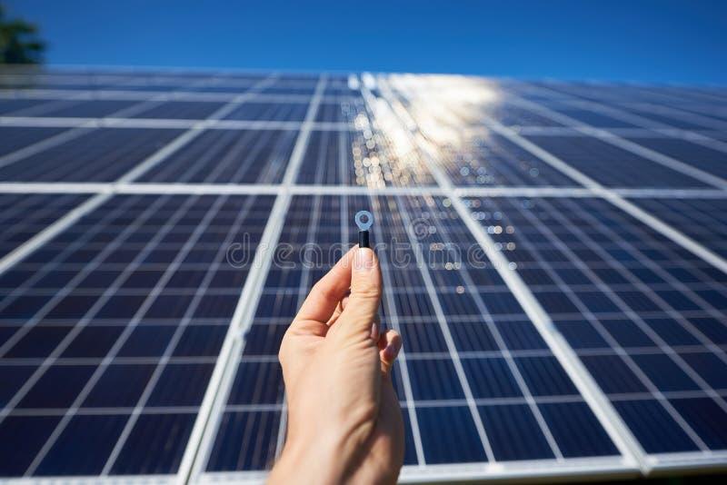 工作者拿着太阳能电池安装的` s手Frontview微小的细节 库存图片