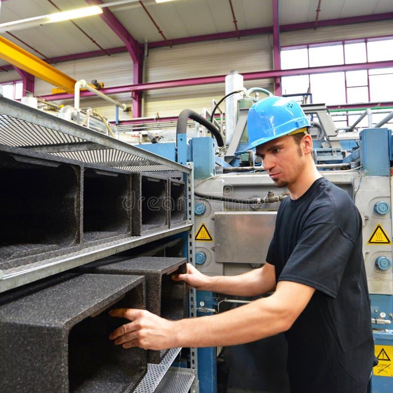 工作者操作在塑料工业的机器-生产  免版税图库摄影