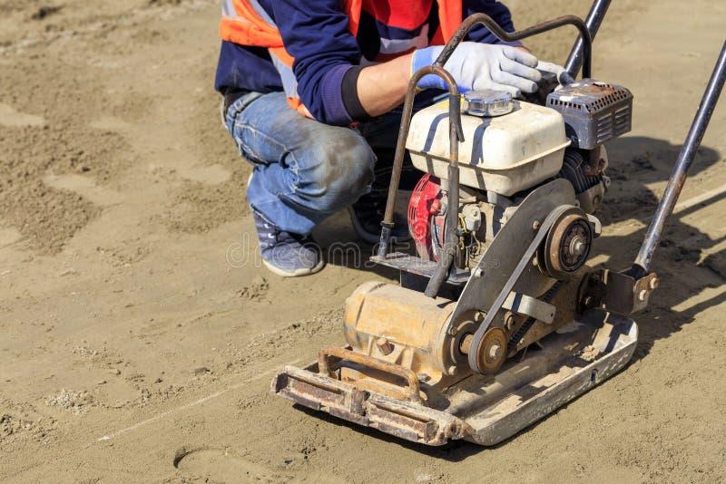 工作者清洗一台老汽油压紧机变紧密含沙土壤 免版税库存照片