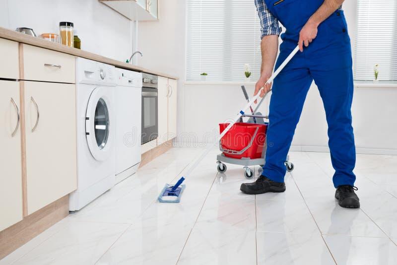 工作者清洁地板在厨房屋子里 免版税库存照片