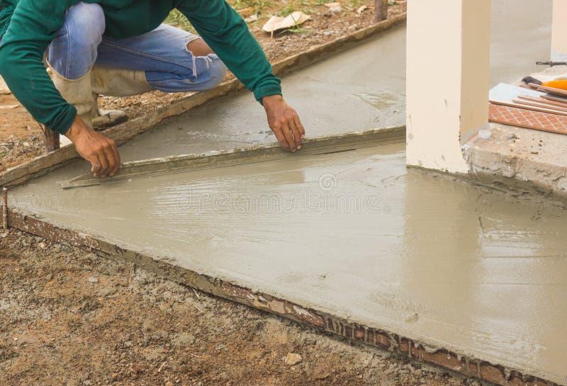 工作者由长的修平刀,工作在地面的膏药水泥的建筑工人的膏药水泥在房子里 图库摄影