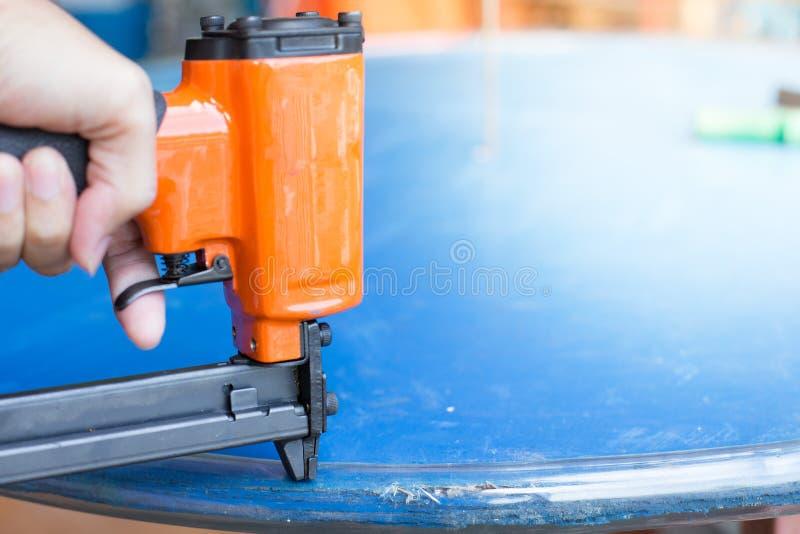 工作者的手使用一杆钉子枪 免版税库存图片