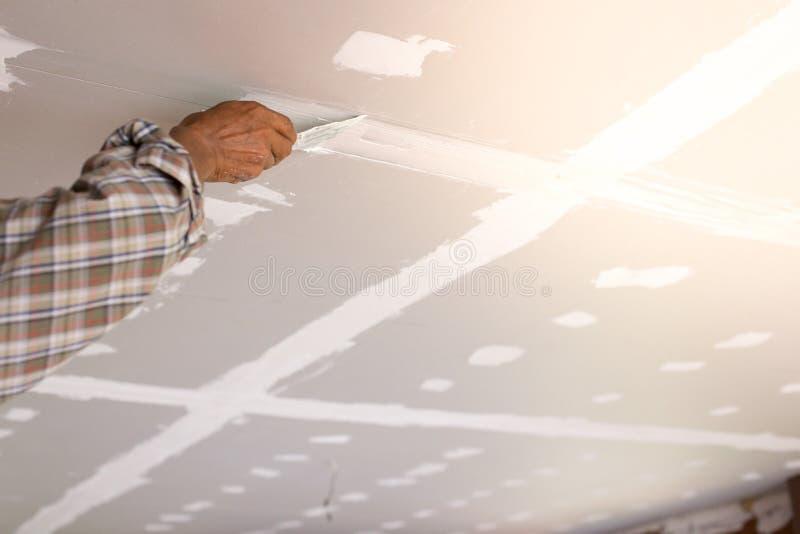 工作者的手修理天花板 免版税库存照片
