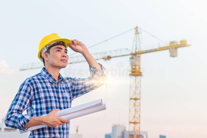 工作者穿戴黄色安全帽画象和拿着与承诺的图纸在工地工作有起重机背景 免版税图库摄影