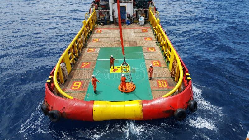 工作者被对近海平台的起重机,由个人篮子的调动乘员组举从乘员组小船到平台 库存图片
