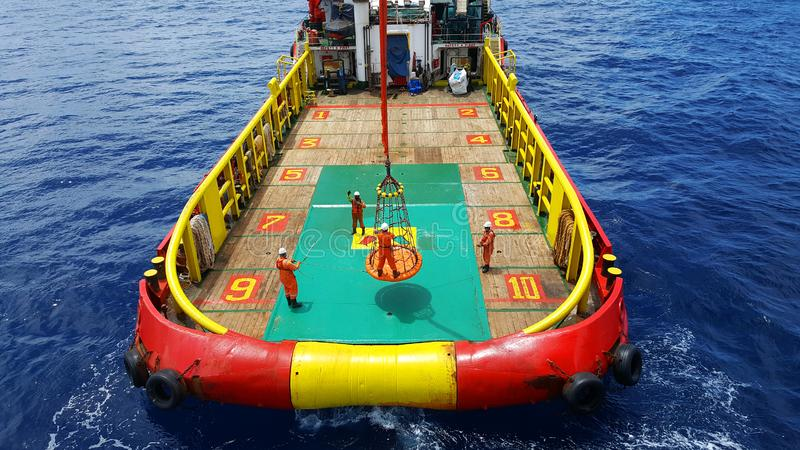 工作者被对近海平台的起重机,由个人篮子的调动乘员组举从乘员组小船到平台 免版税库存照片