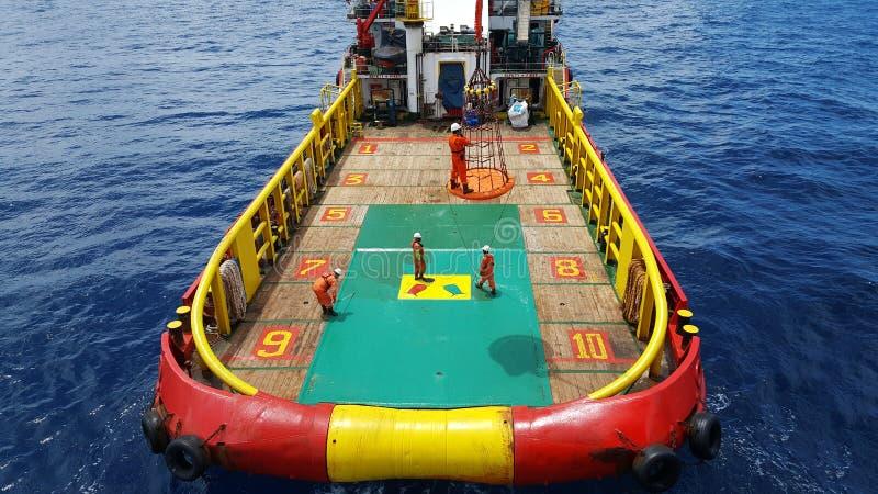 工作者被对近海平台的起重机,由个人篮子的调动乘员组举从乘员组小船到平台 图库摄影