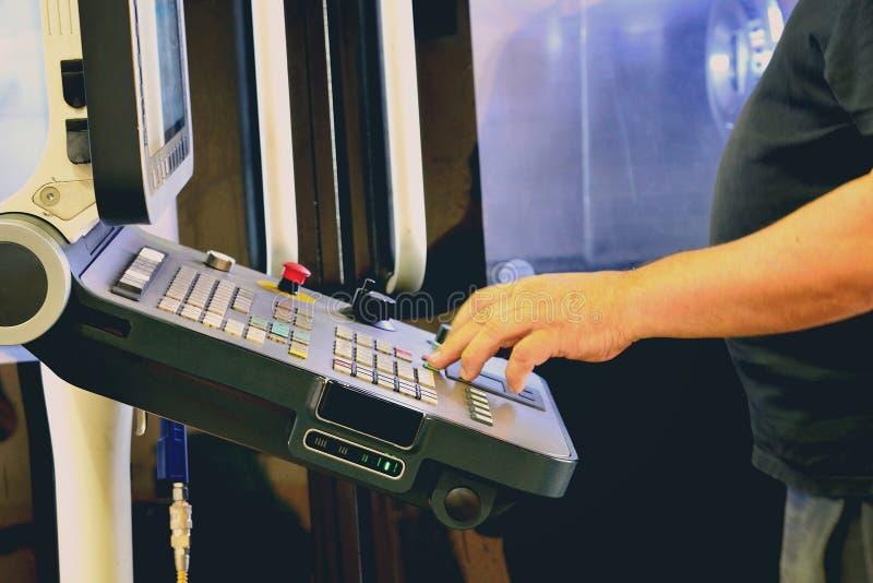 工作者,一个高精密度的CNC机械中心的操作节目的控制板的操作员,处理manufac 免版税库存照片