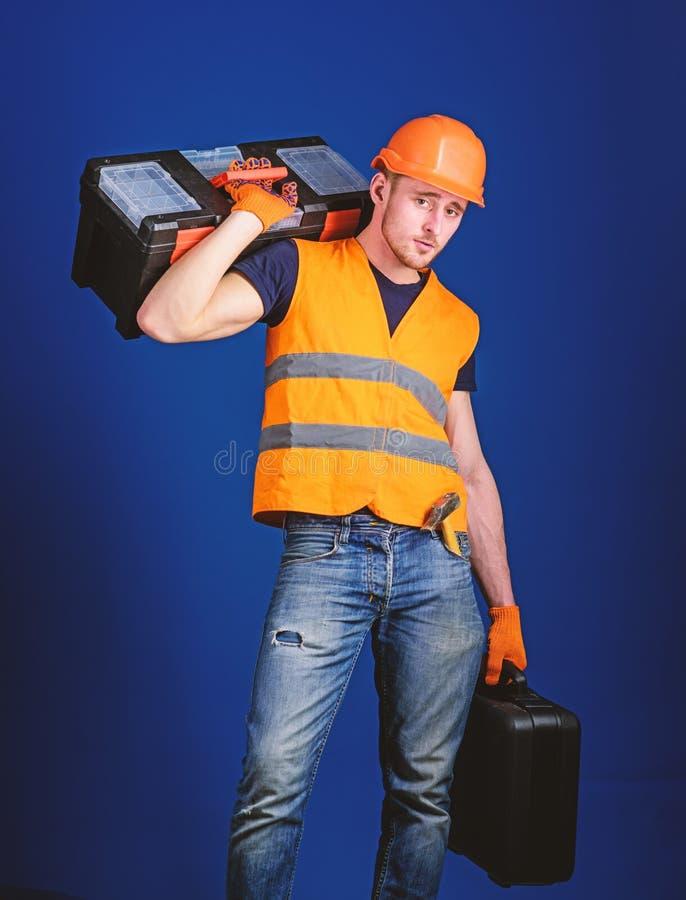 工作者,修理匠,安装工,在镇静面孔的建造者运载在肩膀的工具箱,准备好工作 r 库存图片