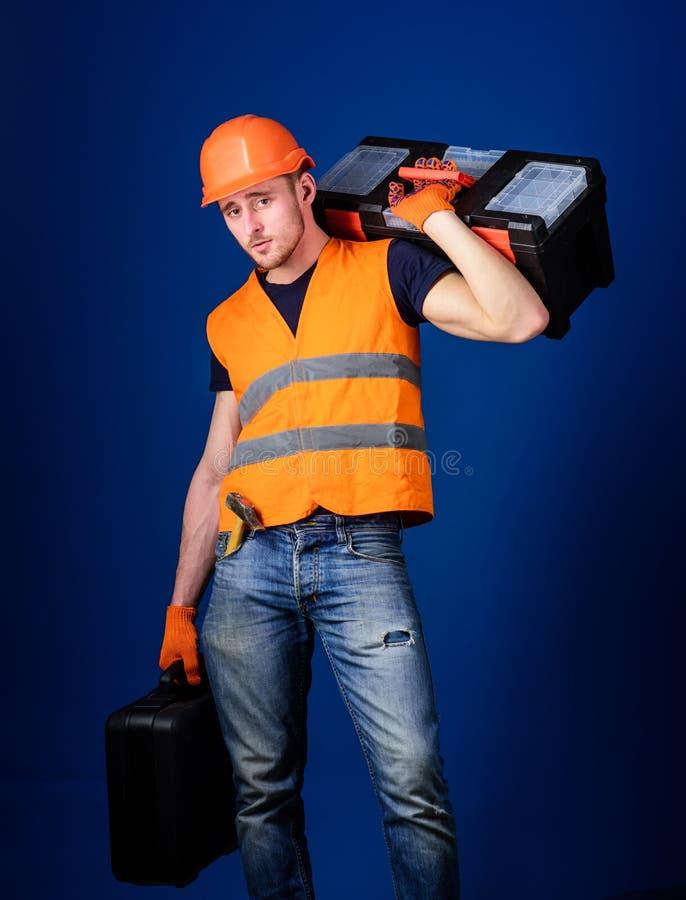 工作者,修理匠,安装工,在镇静面孔的建造者运载在肩膀的工具箱,准备工作 修理公司概念 图库摄影