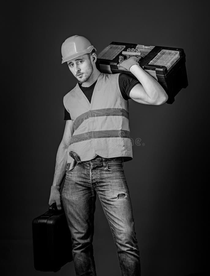 工作者,修理匠,安装工,在镇静面孔的建造者运载在肩膀的工具箱,准备工作 修理公司概念 免版税库存照片