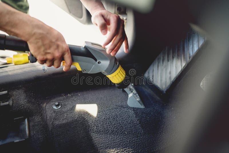 工作者, detailer吸尘的地毯汽车内部,使用蒸汽真空 免版税库存图片