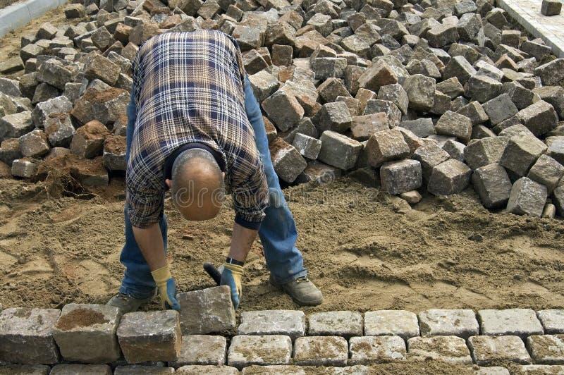 工作者:放置鹅卵石的道路施工人员 库存照片