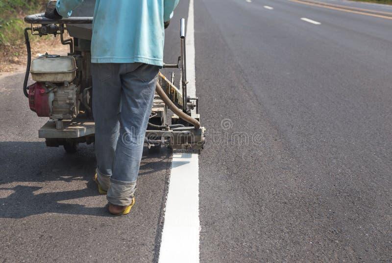 工作者绘画与喷洒的交通线抛出机器 库存图片