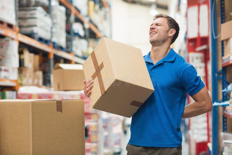 工作者以腰疼,当举箱子在仓库里时 图库摄影