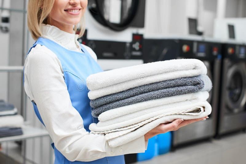 工作者洗衣店女孩在她的手和微笑上的拿着新鲜的毛巾 库存图片