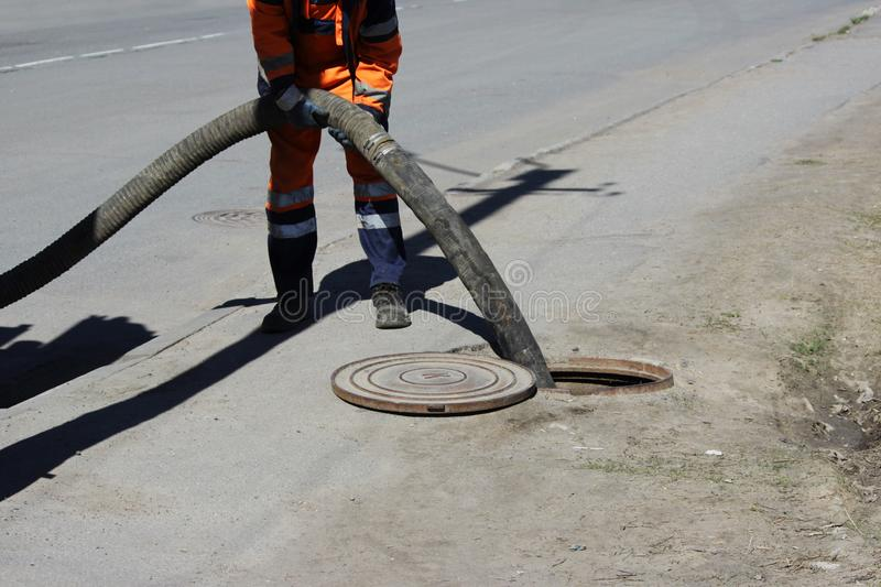 工作者ossenizator抽了污水在下水道系统外面通过在街道的舱口盖 街道清洁的污水工作者 免版税图库摄影