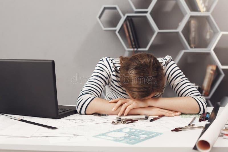 工作职业和劳累过度 关闭有黑发的疲乏的年轻悦目工程师女孩在镶边衣裳说谎 免版税库存图片