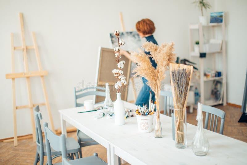 工作艺术家现代演播室内部的妇女画家preparaing的类 库存照片