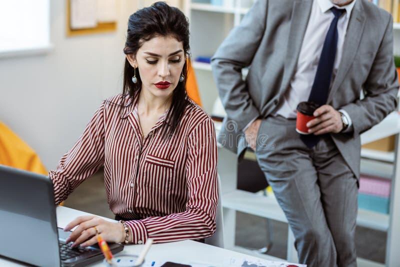 工作被集中的镶边女衬衫的镇静严肃的长发妇女 图库摄影