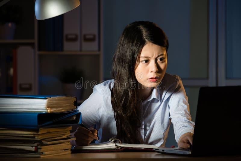 工作超时夜间的亚裔女商人在办公室 免版税库存图片