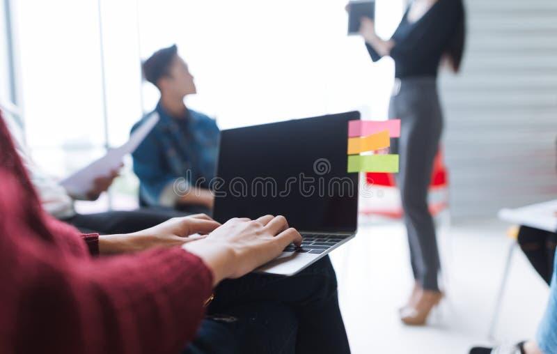 工作通过使用膝上型计算机的商人在候选会议地点 库存照片