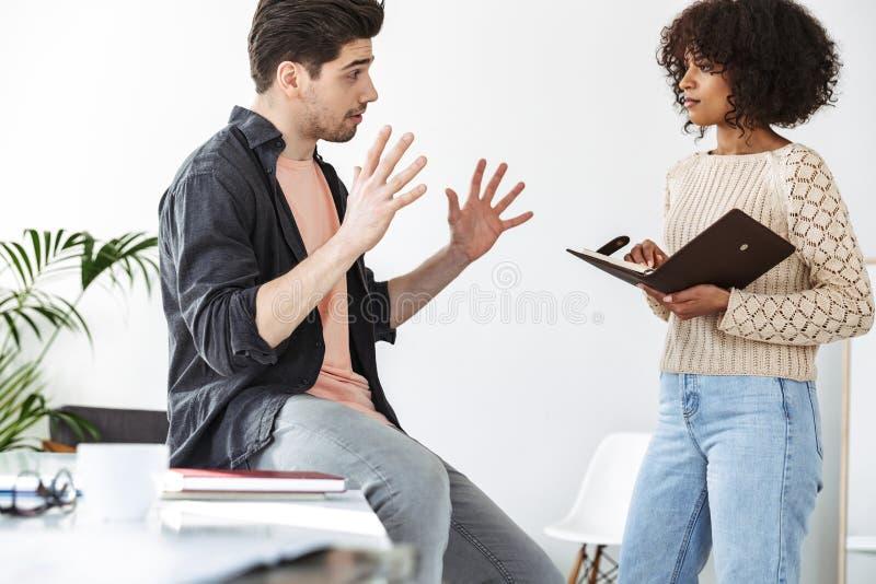 工作镇静被集中的年轻的同事侧视图谈话和 免版税库存图片