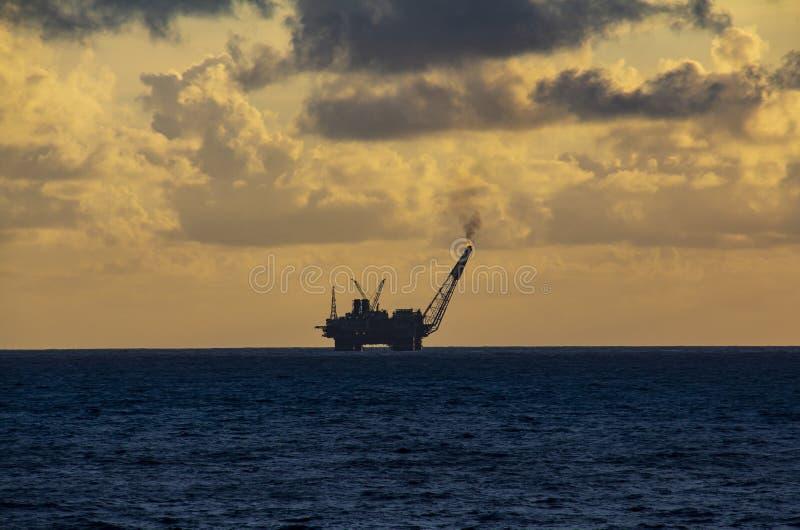 工作面积近海处在公海、石油工业和美好的天和日落,平台 库存照片