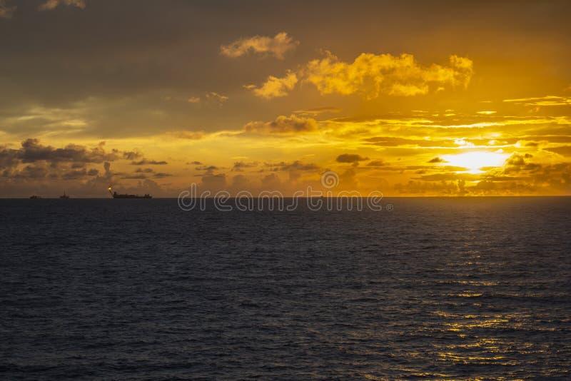 工作面积近海处在公海、石油工业和美好的天和日落,平台 库存图片